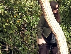 Sexy babe slyly photographed peeing behind a tree