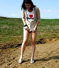 Brunette wets the sand under her feet with her pee